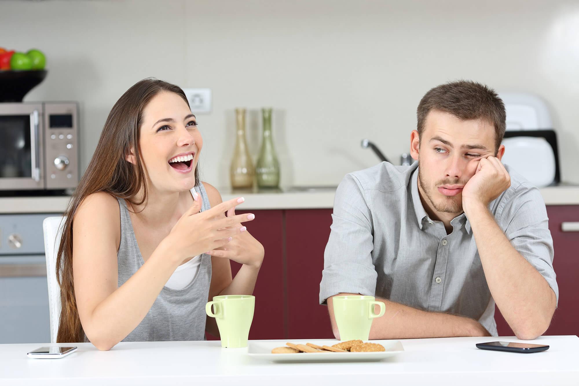 Mann sitzt gelangweilt mit Frau am Tisch