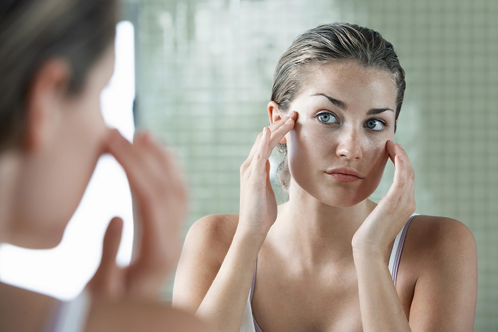 Frau betrachtet sich im Spiegel