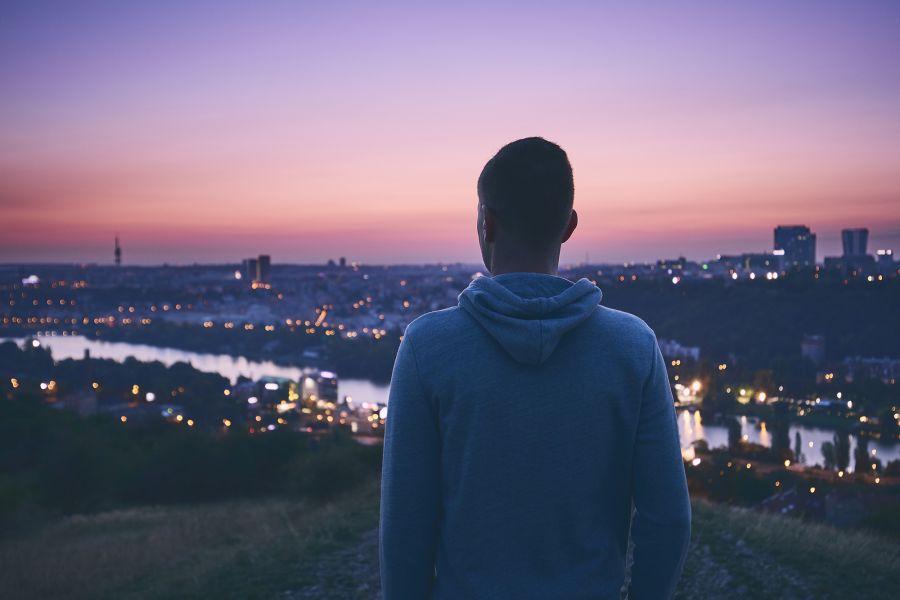 Mann blickt uber Stadt mit Sonnenuntergang